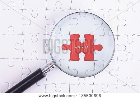 Business Concept - Magnifier Glass on white puzze with AUDIT Word