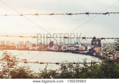 City space of Pattaya city and shore in sunrise, with blurred barbed wire foreground, abstract concepts, vintage tone