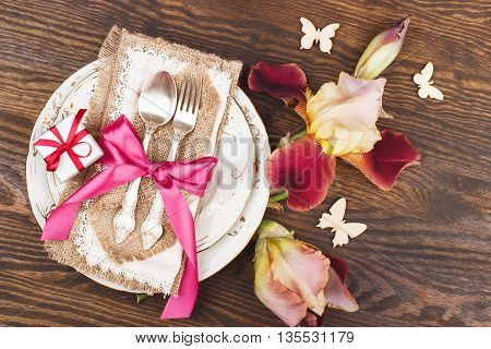 Tableware and silverware with irises on the wooden background