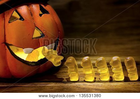 halloween pumpkin eating a row of gummy bear for trick or treat concept
