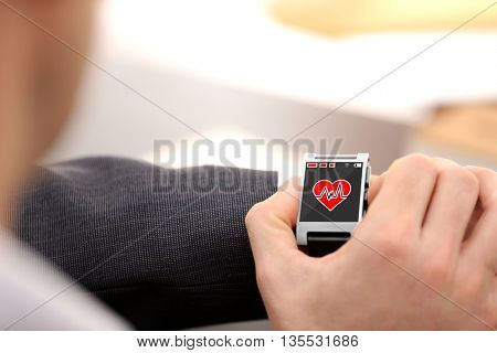 Male hands with heart icon on smart watch on light background