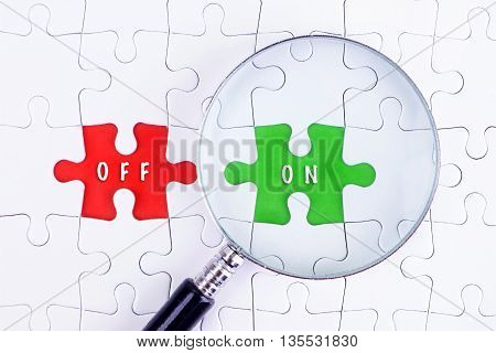 BUSINESS CONCEPT - Magnifying glass on missing puzzle with a word OFF and ON.