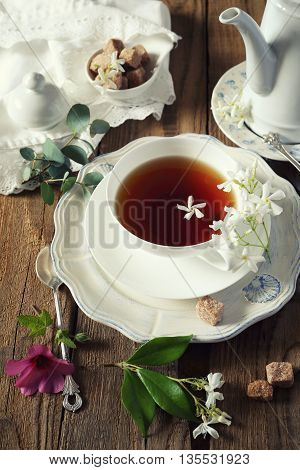 Decorative composition of vintage style: romantic tea drinking with jasmine tea. Toned image