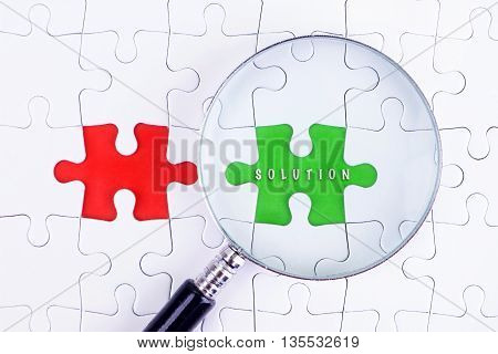BUSINESS CONCEPT - Magnifying glass on missing puzzle with a word SOLUTION