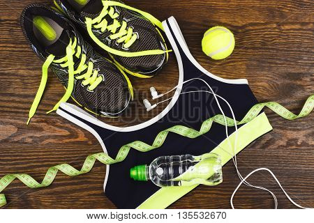 Sports items: sneakers ball and sports bra on the wooden background