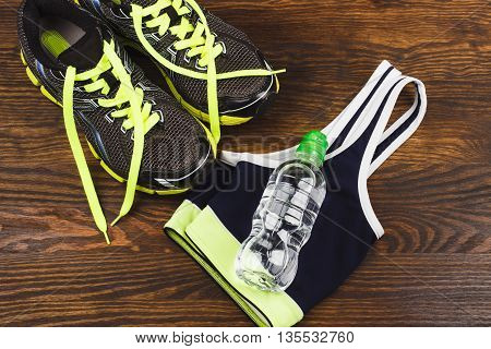 Sports items: sneakers bottle and sports bra on the wooden background