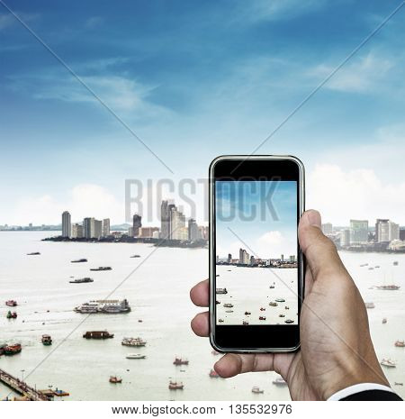 Mobile phone on hand with cityscape view and blue sky, taking photo of the city