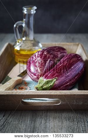 Still life with vegetables: Healthy and delicious graffiti eggplants pink salt and olive oil on gray wooden tray