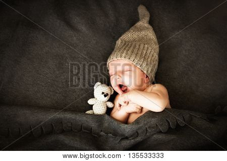 newborn baby sleeping  with a toy next to the  knitted teddy bear and yawns