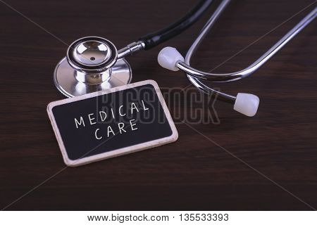 Medical Concept- MEDICAL CARE words written on label tag with Stethoscope on wood background