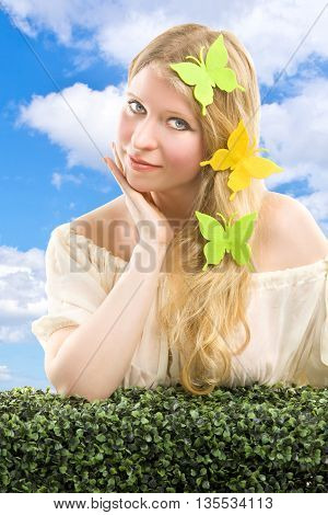 Beautiful blonde woman with butterfly decoration. Outdoor shoot