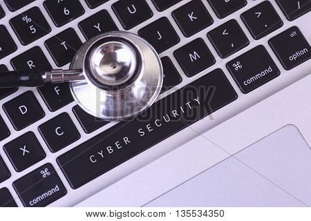 close up of stethoscope and CYBER SECURITY written on laptop keyboard.