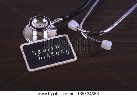 Medical Concept- health history words written on label tag with Stethoscope on wood background