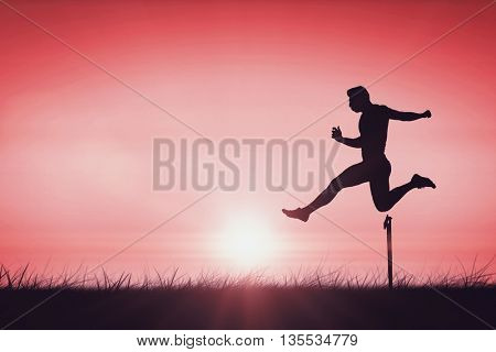 Athletic man practicing show jumping against red sky over grass