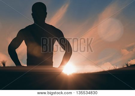 Athlete standing with hand on hip against landscape with sunset