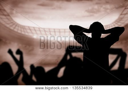 Silhouettes of football supporters against stadium