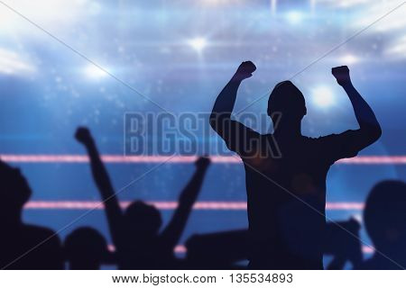 Silhouettes of football supporters against composite image of boxing ring