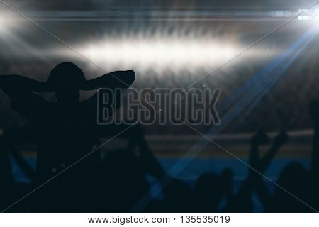 Silhouettes of football supporters against digitally generated image of blue tennis court illuminate by spotlight