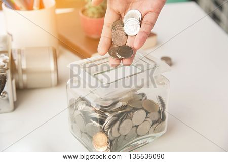piggy bank pile gold coin with hand holding money coin on glass piggy bank. (business bank and finance concept)