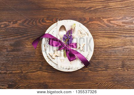 Tableware with violet lupinus and silverware on the wooden background