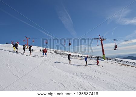 children skiers training on the slope with chairlift in the background and blue sky