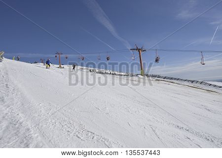 Ski slope with clear blue sky and chairlift with skiers