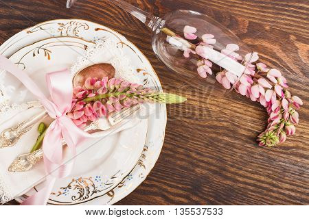 Tableware with pink lupinus, silverware and decorations on the wooden background
