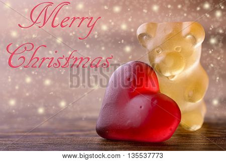 gummy bear with red heart and glitter on wood and merry christmas written