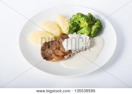 Beef steak with potato garnish served on white plate