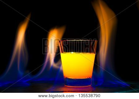 Alcoholic cocktail fruit surrounded by flames on black background