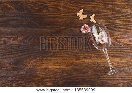 Empty wineglass with decorations on the wooden background