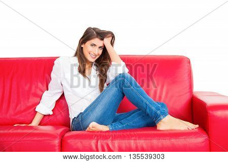 Portrait of beautiful young woman with hand in hair. Full length of happy female is relaxing on red sofa. She is with confident look on her face isolated over white background.