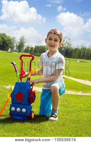 Little boy golfer with his plastic colorful golf set on green field outdoor