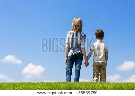 Brother and sister holding hand are in the meadow and watch the clouds in the sky