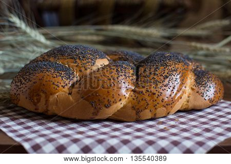 Delicious homemade artisan fresh bread rolls sprinkled with poppy seeds on the background of barley ears on a checkered tablecloth