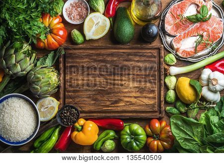 Dinner cooking ingredints. Raw uncooked salmon fish with vegetables, rice, herbs and spices over rustic wooden background, top view, copy space. Chopping board in center