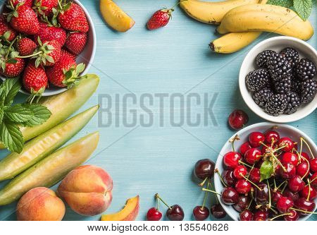 Healthy summer fruit variety. Sweet cherries, strawberries, blackberries, peaches, bananas, melon slices and mint leaves on blue backdrop with copy space in center, top view