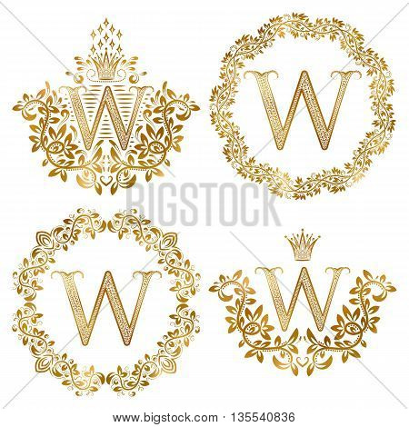 Golden W letter vintage monograms set. Heraldic coats of arms and round frames.