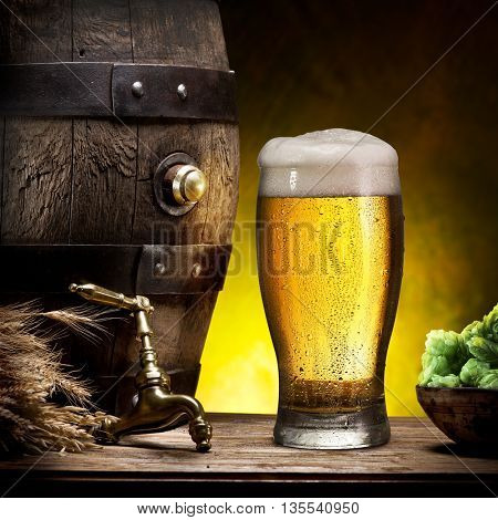 Glass of light beer and barrel on the wooden table.