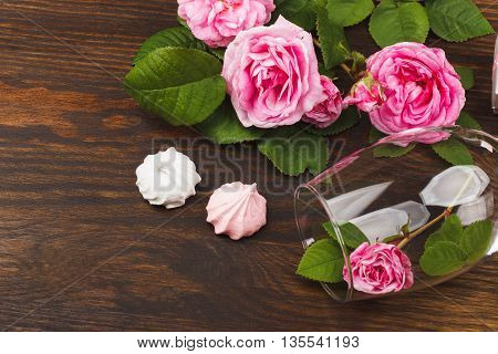 Empty wineglass with small light pink rose inside and meringues on the wooden background with blank copy space area for text or slogan
