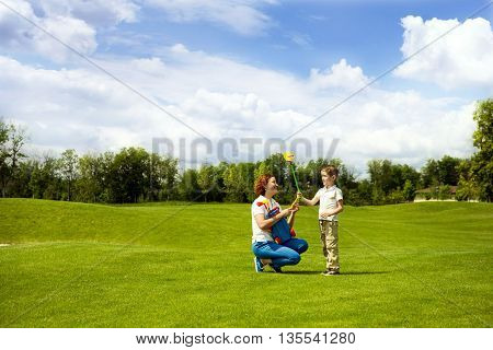 Mom and son playing in the children's golf. Concept of friendly family