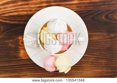 White cup with light pink and white meringues on the wooden background with blank copy space area for text or slogan
