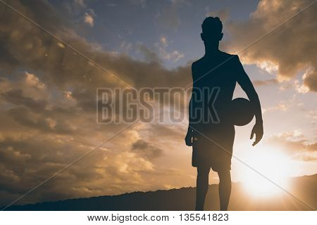 Sportsman holding a basketball against clouds