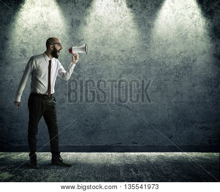 a man screams with megaphone on the wall