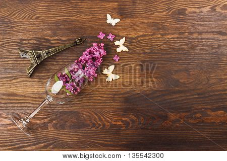 Wineglass with lilacs miniaturized Eiffel tower and butterflies decorations on the wooden background