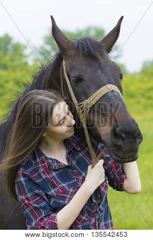 Teenager girl in plaid shirt hugs the horse