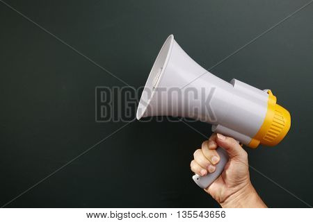 man holding megaphone in front of blackboard
