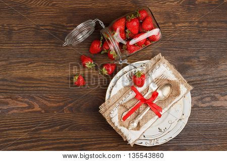 Tableware and silverware and a bank with red ripe strawberries on the wooden background