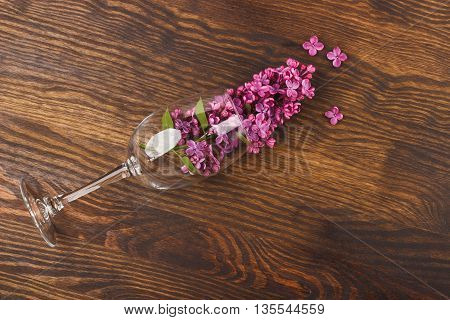 Wineglass with violet lilacs on the wooden background