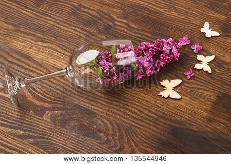 Wineglass with lilacs and butterflies decorations on the wooden background